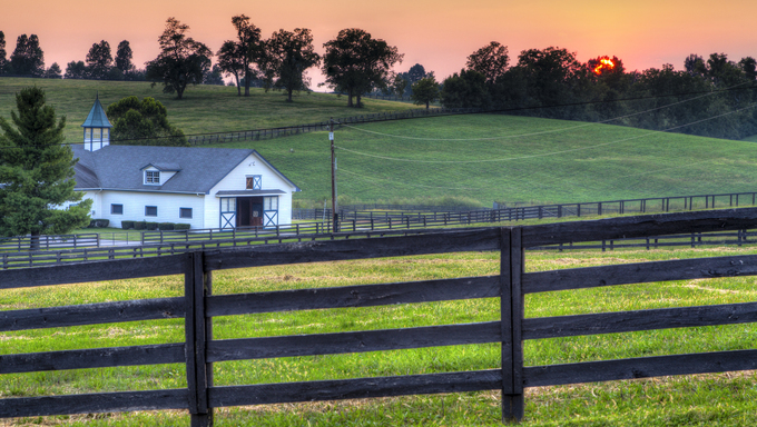Sunset behind the fields of a horse farm in Kentucky