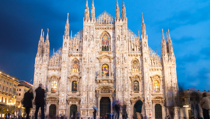 Milan Cathedral (Duomo di Milano) is the gothic cathedral church of Milan, Italy. Shot in the dusk from the square ful of people.