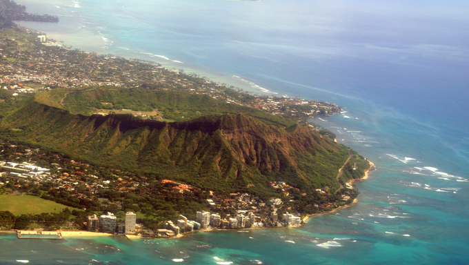 Aerial view of Diamond Head Crater, Kapiolani park, Black Point and Kahala on Oahu with wave braking against reef on nice day.