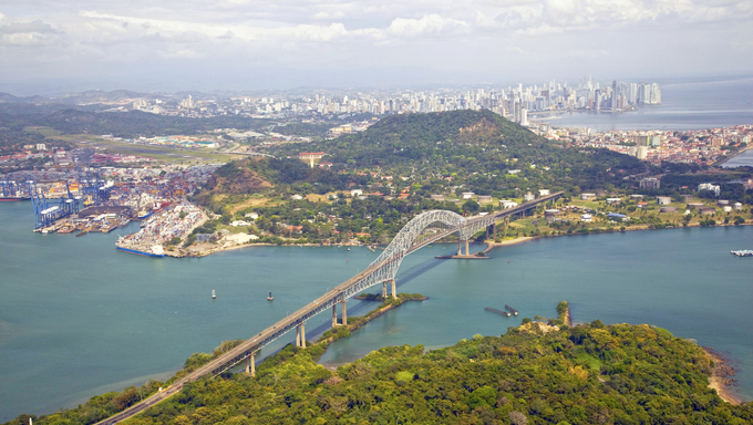 Aerial view of the Bridge of the Americas at the Pacific entrance to the Panama Canal with Panama City in the background.