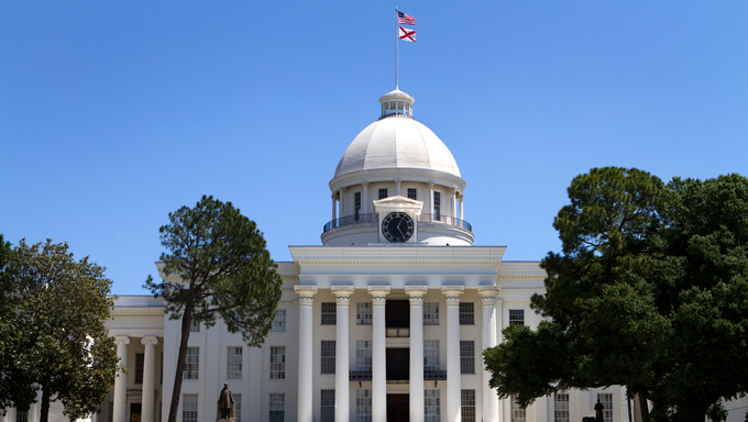 Alabama State Capitol building and grounds in Montgomery, Alabama, USA against a blue sky.