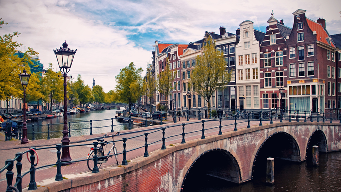 Beautiful view of Amsterdam canals with bridge and typical dutch houses in Holland.