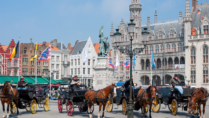 Bruges, Belgium. Horses and carriage for hire on the Market Square, one of the main sightseeing places of Bruges.