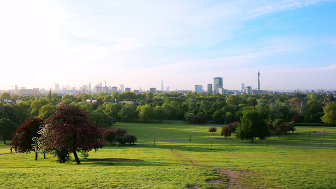 Breath-taking panoramic scenic view of London cityscape seen from beautiful Primrose Hill in St. Regents park on a sunny summer morning.
