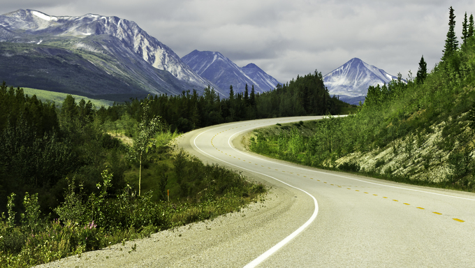 Curved asphalt road in the high mountains of Alaska.