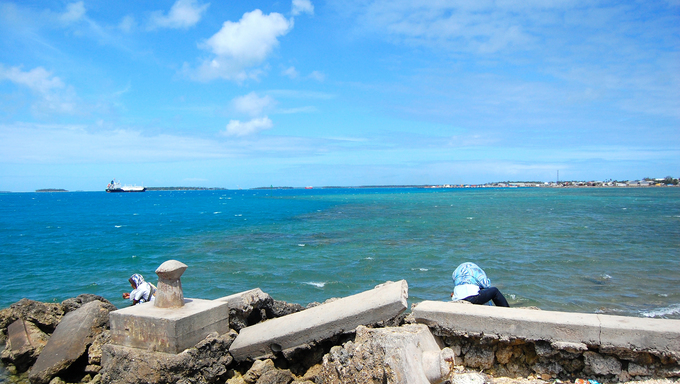 People sit at ocean coast, Tonga capital town