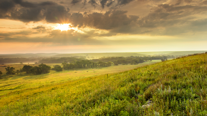 A light fog and heavy dew fills the valley as the sun warms the sky on a mild summer morning in the Kansas Tallgrass Prairie Preserve.