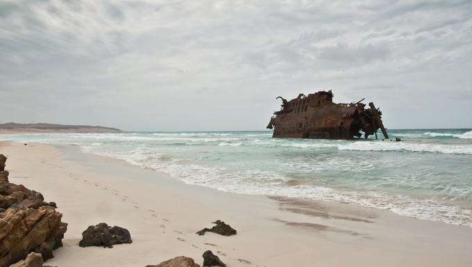Shipwreck worned out by the wether and the waves of the ocean on the coast of the island of Boa Vista in Cape Verde on a cloudy and rainy day