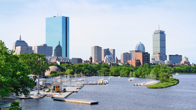 Boston back bay with a sailing boat and an urban building city skyline in the morning.