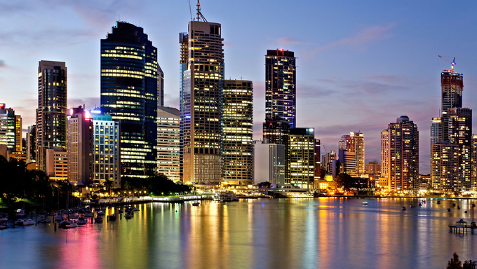 Brisbane city reflected in the river at sunset with colored lights