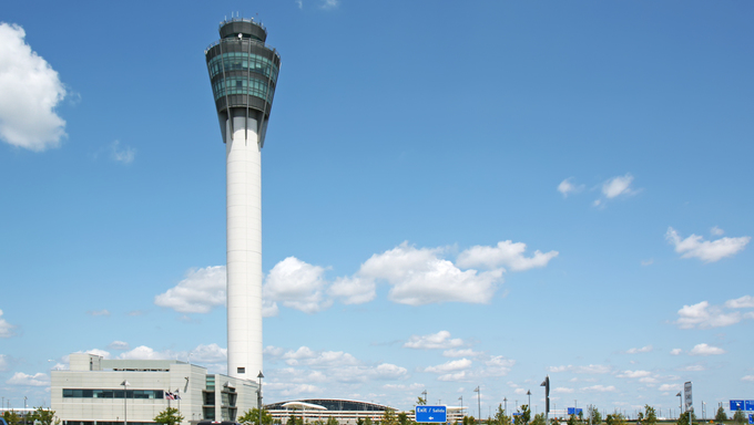 Air traffic control tower at Indianapolis International airport with blue sky and pavement