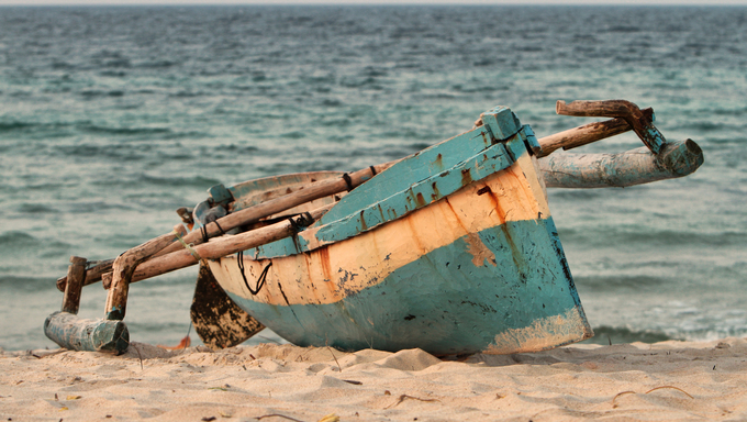 An indigenous fishing boat or dhow is lying on the beach sand of Pemba, mozambique.