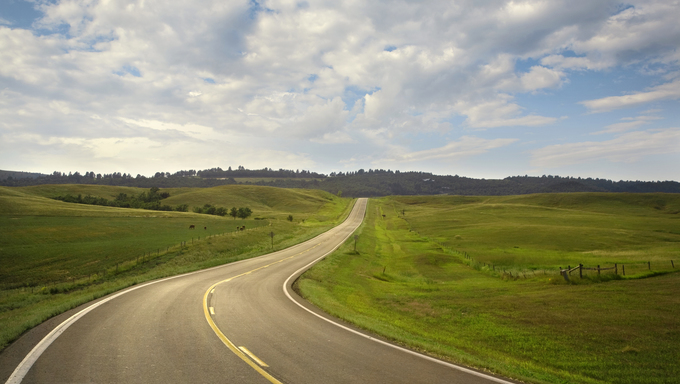 A curving road in the Black Hills area of South Dakota on a sunny afternoon.