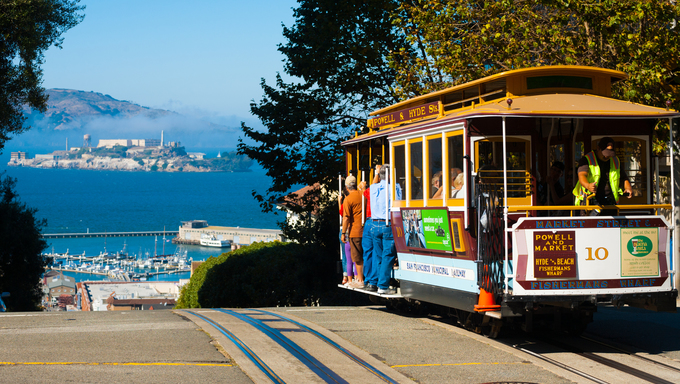Powell Hyde cable car, an iconic tourist attraction, descends a steep hill overlooking Alcatraz prison and San Francisco Bay.