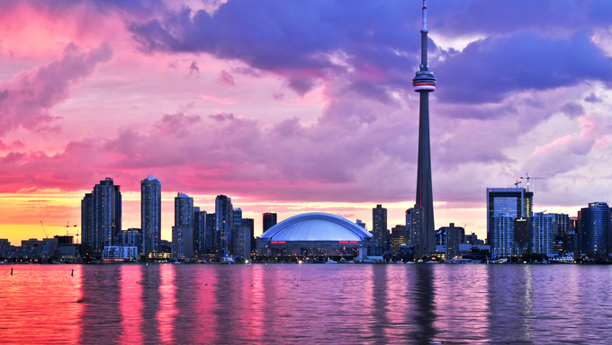 A scenic view from the Toronto City Waterfront displaying Toronto's skyline at sunset.
