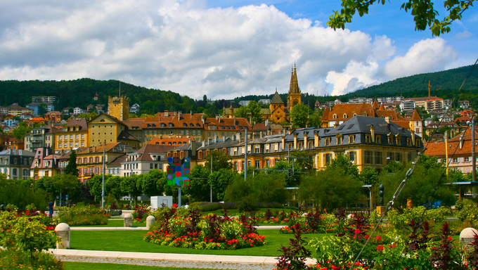 Panoramic view of city Neuchatel in Switzerland. Colorful sunny day with beautiful park and old architecture.