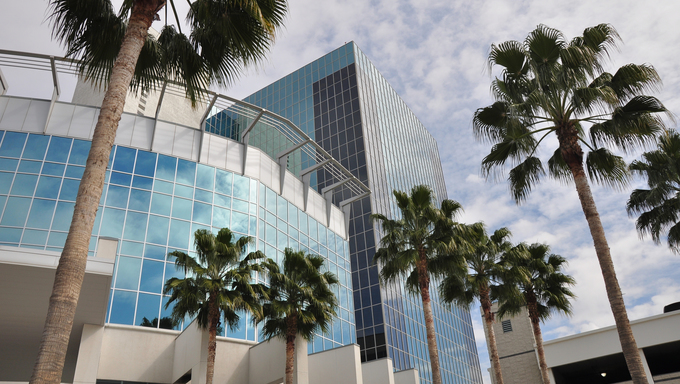 Palm trees mix with a modern glass office tower in Riverside, California.
