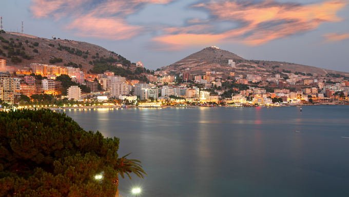 summer fun city of Saranda in Albania at sunset with all lights flashing with hotels lining along sea front
