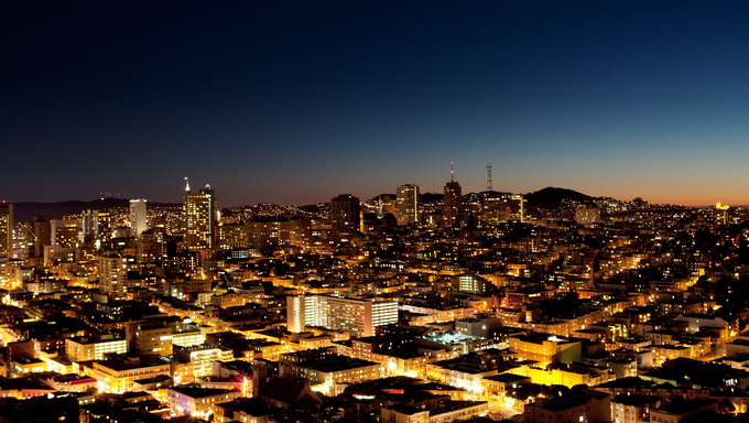 A view of a city at night with a sunset on the horizon of San Jose.