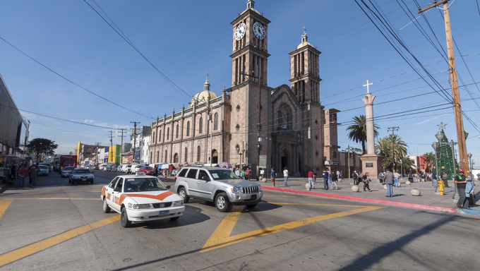 Cathedral of Our Lady of Guadalupe in downtown Tijuana shows signs of the Christmas season with kiosks along the sidewalk. Sellers offer Christmas related merchandise as people and traffic hurry by.