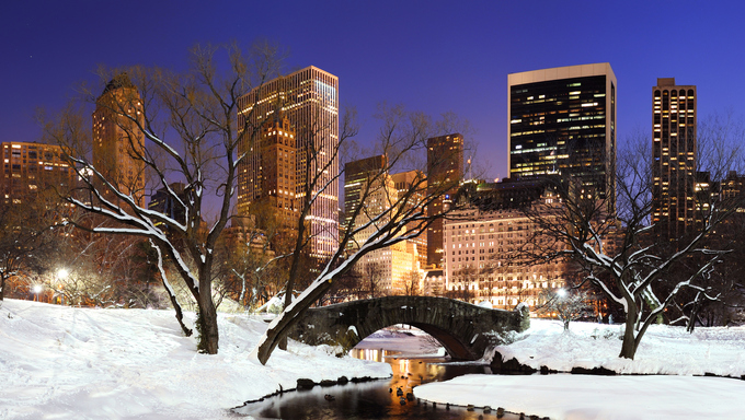 New York City Manhattan Central Park panorama in winter with a snowy bridge. Freezing lake and skyscrapers at dusk.