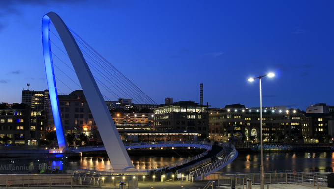 Night view of Newcastle and the Millennium bridge lit up in blue.