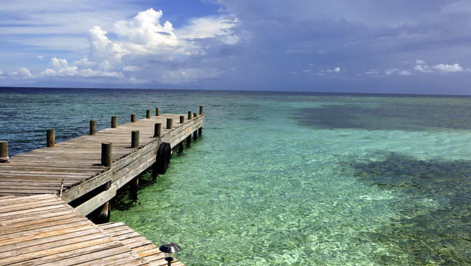 An empty dock leading out into the Caribbean Sea.