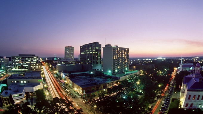 Florida's capitol, Tallahasse at night. The Tallahassee skyline downtown.  Monroe St runs south to the left and Park runs westward to the right toward FSU which has it's stadium lights on during football Saturday night.