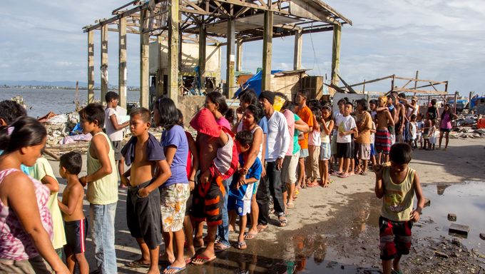 Survivors of Typhoon Haiyan lining up for food, in the background was the remain of a house that was damaged by Typhoon Haiyan (local name Yolanda) that struck central Philippines last November 8, 2013 killing more than 6,000 people.