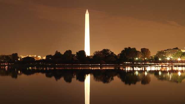 Washington Monument reflected in water at night in Washington, DC, USA.