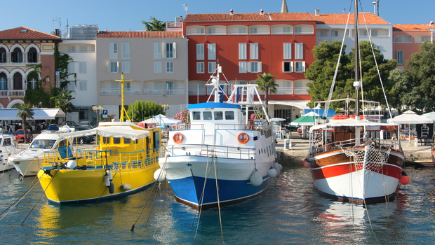 three colorful ship moored in a small european town