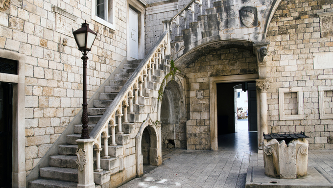 Old courtyard with a staircase and a well in Trogir Croatia