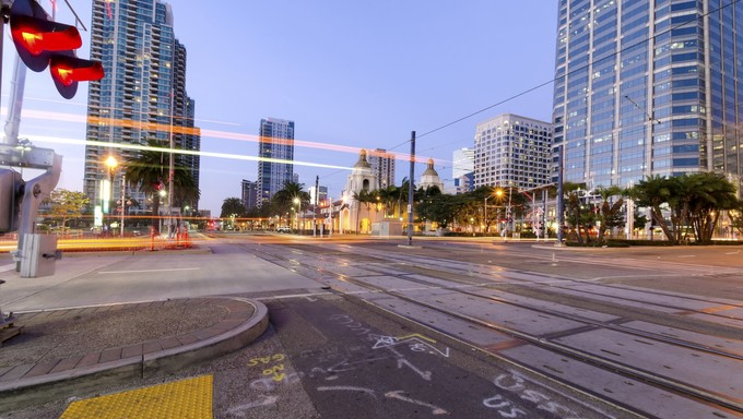 A street view of Downtown San Diego, California, USA, at dusk. A night view of the transportation, city lights and skyscrapers and local buildings in the Marina's waterfront.