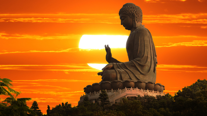 Buddha statue over scenic sunset sky background