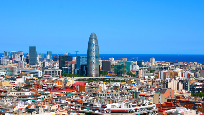 Classic view of hot Barcelona in Spain. Many buildings with interesting architecture. Torre Agbar in center with other houses in downtown of Barcelona. Mediterranean sea in the background.