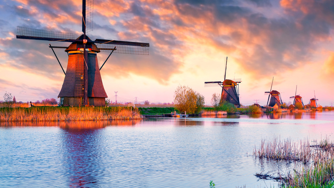 Colorful spring sunset in Netherlands. Dutch windmills at Kinderdijk, an UNESCO world heritage site.