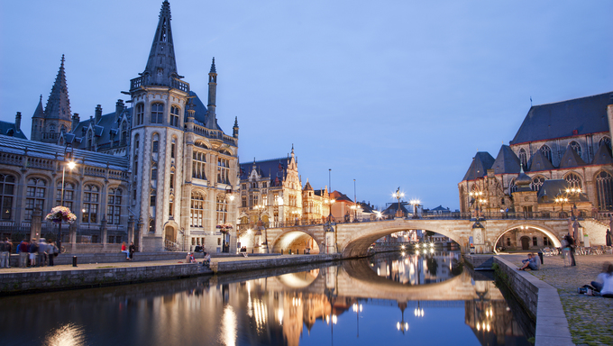 West facade of Post palace and Michael's bridge with the canal in evening from Graselei street in Gent, Belgium.