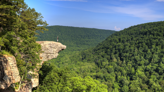 This famous place on the Whitaker's Point trail is the number 1 most photographed spot in Arkansas. A hiker enjoys the view standing hundreds of feet above the Ozark mountains forest below.