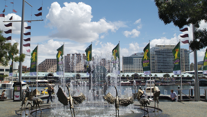 Fountain with crane sculptures and view to different restaurants in the Darling Harbour leisure and retail precinct.