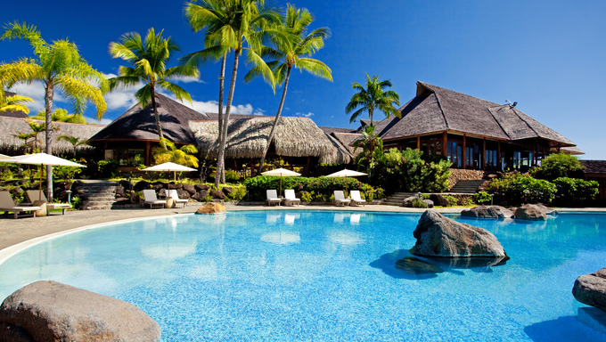 Palm trees hanging over stunning hotel pool with rocks