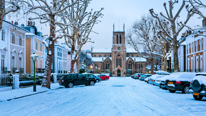 Snow covered, cosy street in Holland Park, London. St James's Church in the middle.