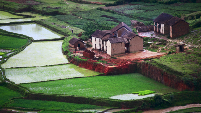 Green hills with red soil, green rice and villages with traditional houses.