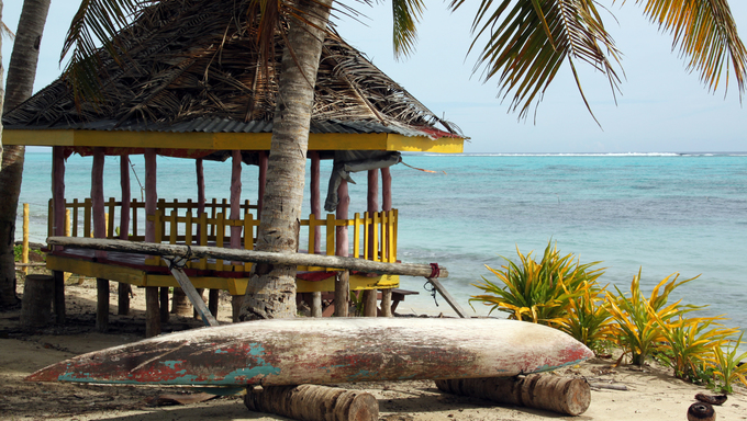 Hut and boat under palm tree on the beach in Savaii, Samoa