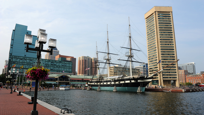 View of Baltimore Harbor with USS Constelation Ship and office buildings in the background.