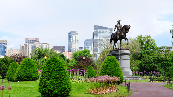 George Washington statue, the famous landmark in Boston Common Park with city skyline and skyscrapers.