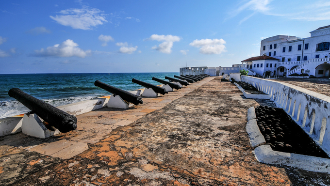 Cannons overlooking from Cape Coast Castle. Cape Coast Castle is a fortification in Ghana built by Swedish traders for trade in timber and gold. Later the structure was used in the trans-Atlantic slave trade.