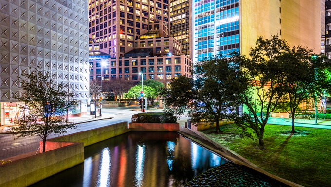 Buildings and pond at Thanks-Giving Square at night in Dallas, Texas.