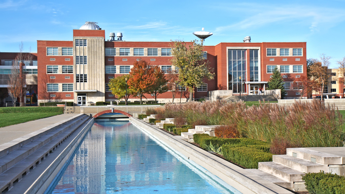 Lilly Science Hall and reflecting pool on the campus of the University of Indianapolis in Indiana with landscaping of the Smith Mall against a background of blue sky and white clouds