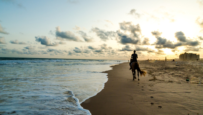 Silhouette of a man riding a horse on the shores of Obama Beach in Cotonou, Benin.
