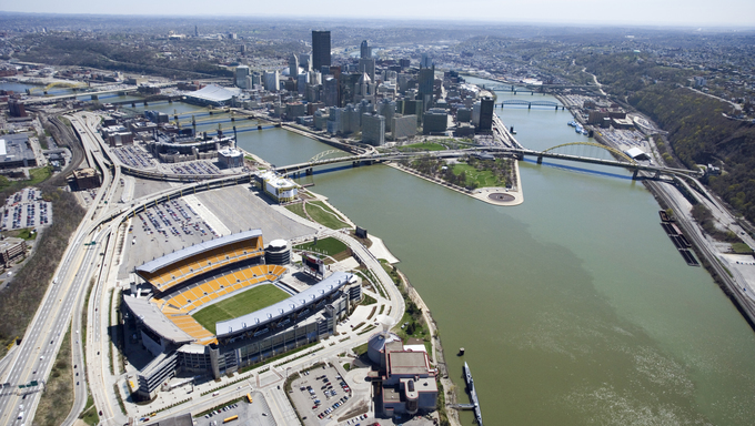 Aerial view of Pittsburgh, Pennsylvania with skyscrapers and stadium and rivers.